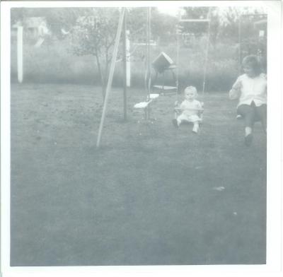 Alice baby on swing with Joann in Nanny's backyard